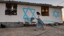 A young woman walks past a simple housing unit in the settlement of Givat Evyatar, West Bank, on July 1.