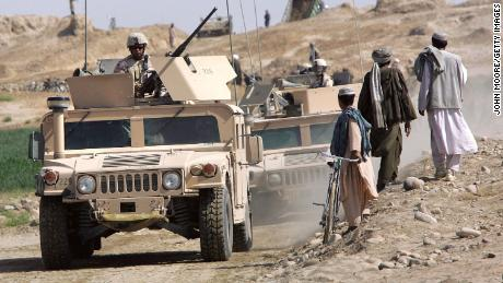 A US Army convoy drives near Lashkar Gah in Afghanistan's southern Helmand province in April 2006. An explosives-packed car detonated near a US base there that month, injuring members of the US military and a team who were training leaders of the Afghan Eradication Force.