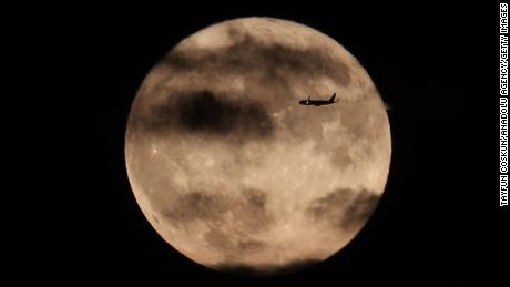 An aircraft flies over the moon of the harvest as it rises behind the Statue of Liberty on October 1, 2020 in New York City.