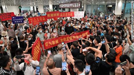 """The crowd carried banners and placards """"welcome home meng wenzhou""""  They wait for Huawei executive Meng Wanzhou at an international airport in Shenzhen Bao on September 25."""