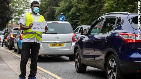 A Shell garage employee holds a sign on the side of the road informing a queue of traffic that they do not have unleaded petrol on September 25, 2021, in Blackheath, London.
