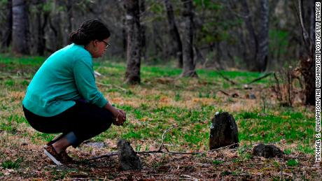 Bethany Pace  kneels at the simple stone monuments that mark the graves of slaves that were her kin, in Sweet Briar, Virginia, in 2015.