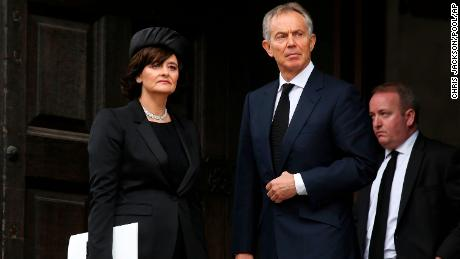 Former British Prime Minister Tony Blair and his wife Cherie Blair leave a funeral on April 17, 2013.