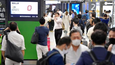 The entrance of JR Shimbashi station in Tokyo is crowded with passengers as the train services are suspended following an earthquake on Thursday.