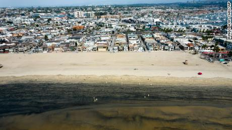 Workers in protective suits clean the contaminated beach after an oil spill in Newport Beach, California, on Wednesday, October 6, 2021.