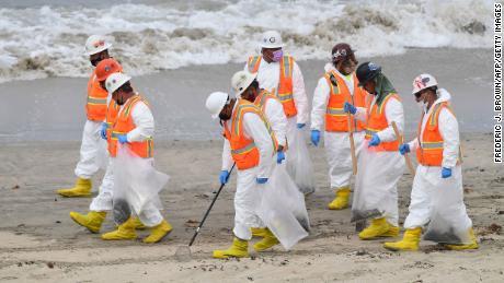 A cleanup crew works on the beach on Thursday, October 7, 2021 in Huntington Beach, California.
