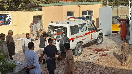Afghans stand next to an ambulance after an attack on a Shia mosque in Kunduz.