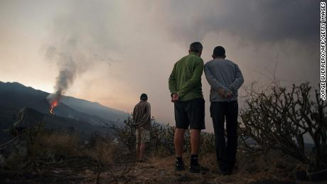 People watch the volcano spew lava, ash and smoke on October 10th.