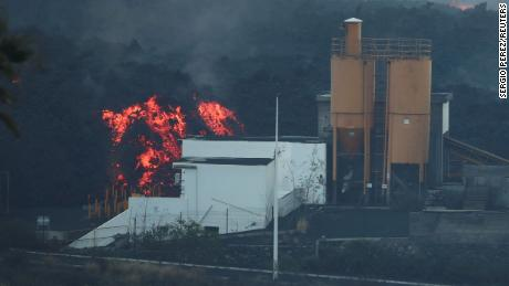 Lava rolled past a cement factory on Monday as the Cumbre Vieja volcano erupted on the Canary Islands of La Palma.