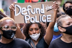 """MANHATTAN, NY - JUNE 19: An African American protester wears a mask and holds a homemade sign that says, """"Defund the Police"""" as they perform a peaceful protest walk across the Brooklyn Bridge. (Photo by Ira L. Black/Corbis via Getty Images)"""