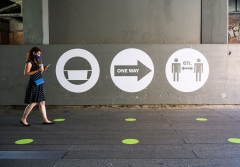A woman passes a social distancing sign. (Photo credit: Noam Galai/Getty Images)