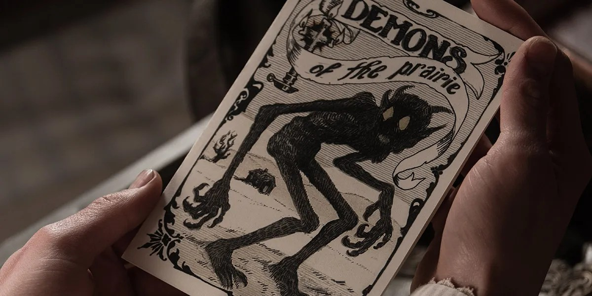 """The Wind (2018). A close up on a pair of hands holding a piece of white card with a black ink illustration of a monstrous creature with large blank eyes, and the caption """"Demons of the prairie"""""""