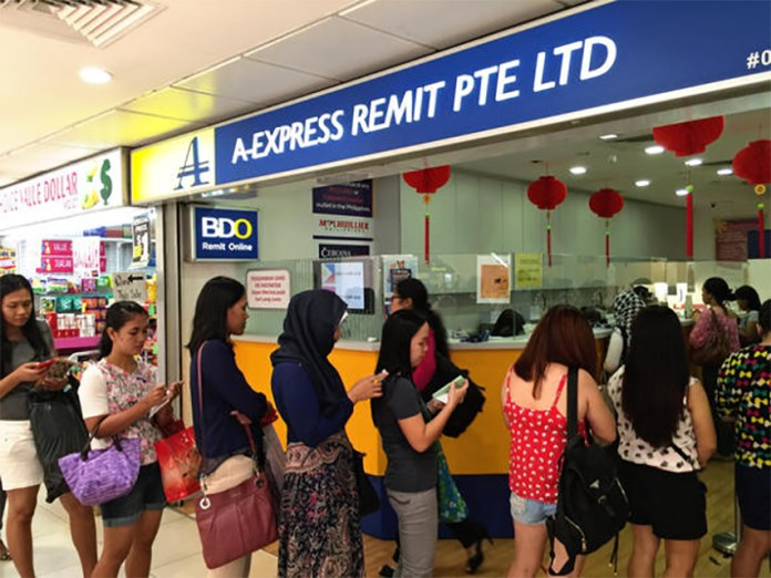 Domestic workers lining up at a money remittance branch at a shopping mall popular with Filipino domestic workers in Singapore's Orchard Road.