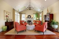 traditional living room with coral colored comfy chairs ...