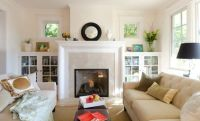 Bookshelves with glass doors flanking the fireplace in the ...