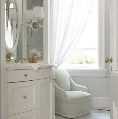 bathrooms - white curved bathroom vanity cabinet white gray carrera marble countertops marble floors soft blue chaise lounge silver sconces oval mirror sheer white drapes blue walls paint color bathroom