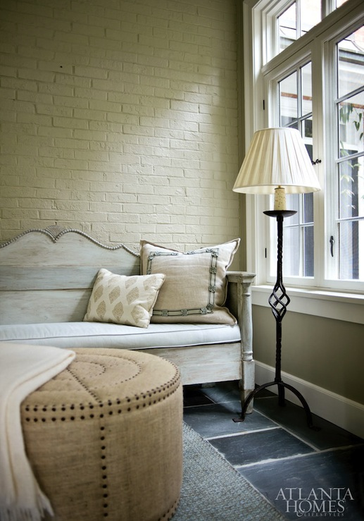 living rooms - Burlap Bullseye Ottoman exposed brick wall painted yellow white washed settee iron floor lamp  Beth Ervin - Chic small living
