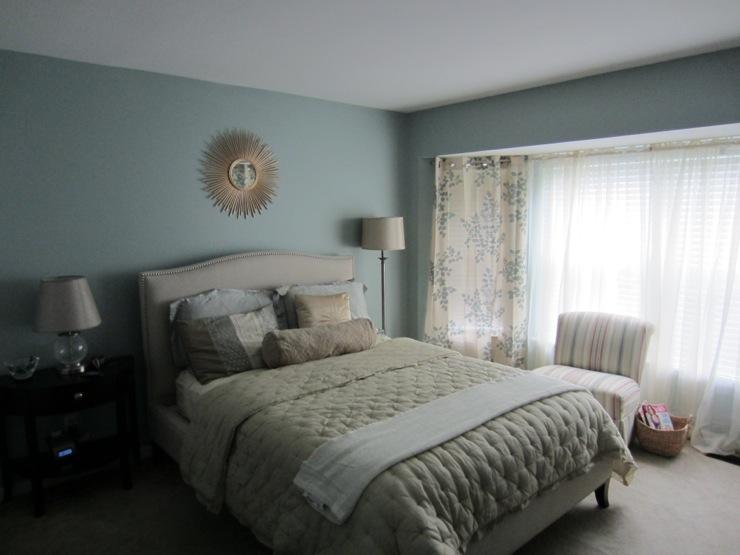 Light blue bedroom with sunburst mirror