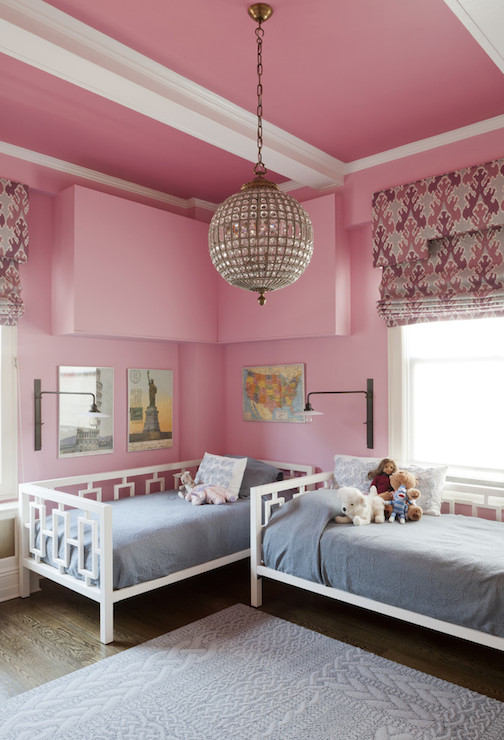 Girls bedroom with swing-arm sconces, pink walls, and two West Elm Daybeds. By Lauren Rubin Architecture Via Decorpad.