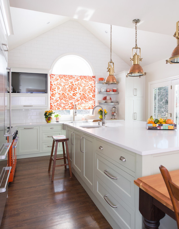 Green and orange kitchen features a cathedral ceiling