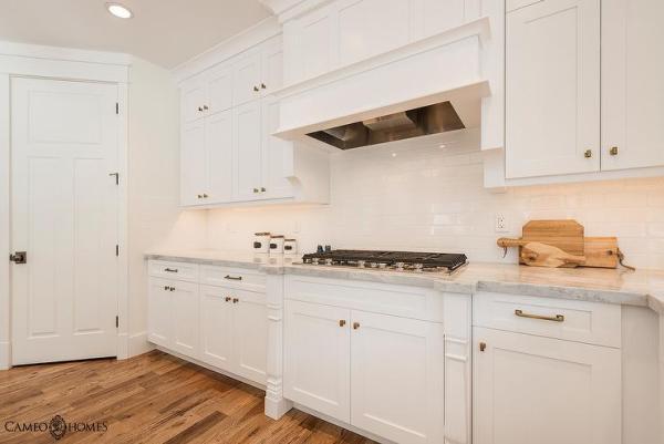 white kitchen cabinets with subway tile backsplash White Kitchen With Brass Accents Design Ideas
