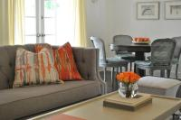 Gray and orange living room features a gray tufted high ...