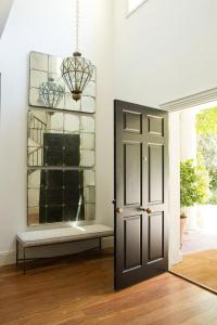 Two Story Foyer with Stacked Mirrors Over Bench ...