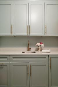 Gray Laundry Room Cabinets with Long Brass Pulls ...