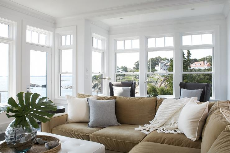 camel and gray living room small furniture for sale design ideas seaside with transom windows surrounding a velvet sectional topped ivory pillows beside white tufted ottoman as table