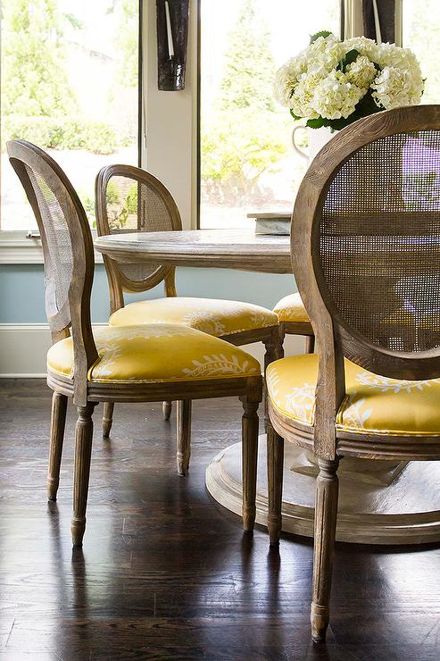 Round Marble Top Dining Table with Round Cane Back Chairs and Yellow Seat Cushions