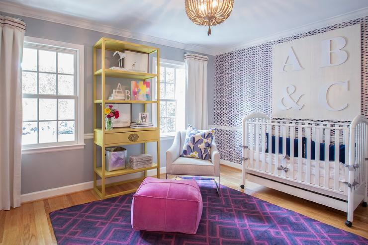 blue nursery chair ikea covers leigh on sea rail design ideas pink and purple features wallpapered accent wall finished with a lined white crib wheels adorned cobalt velvet