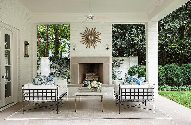 Covered Patio with White Brick Fireplace and Gold Sunburst