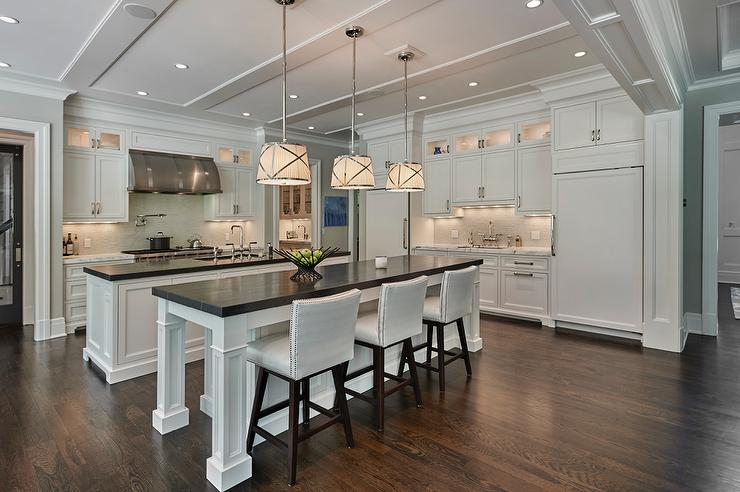 white kitchen islands wall units side by with honed black marble countertops