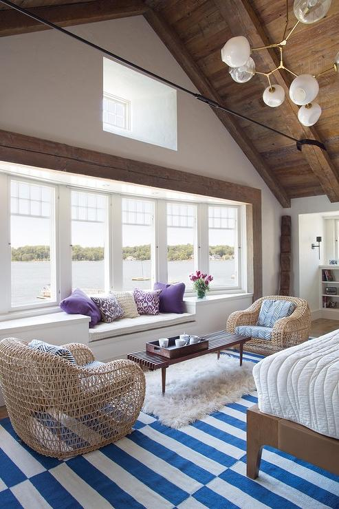 Lakeside Bedroom Sitting Area with Built In Window Seat Lined with Purple Pillows  Transitional
