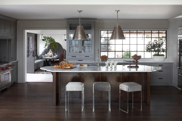 Dark Stained Kitchen Island With Oval Countertop And Backless Lucite