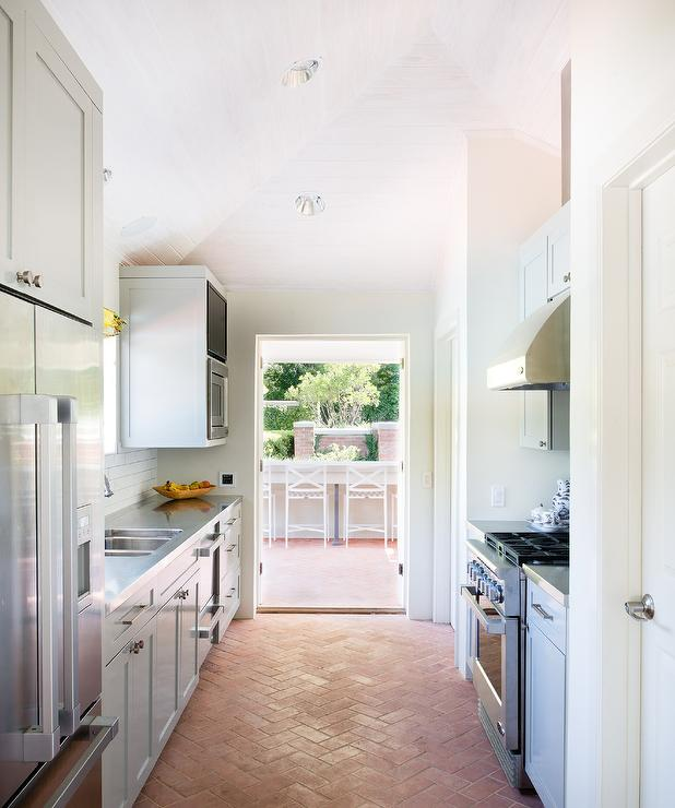 gray galley kitchen with red brick