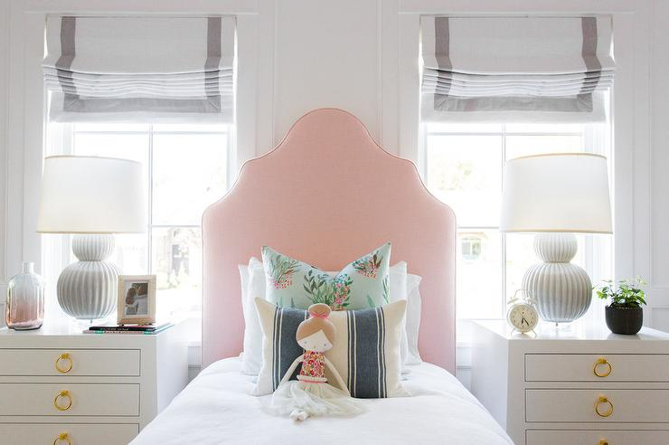 pink headboard with white nightstands