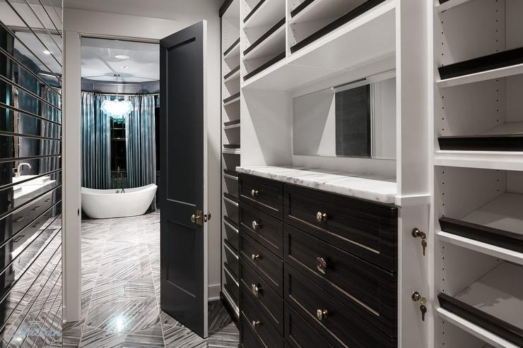 gray chair and a half revolving below 2000 walk in closet with black white harlequin tiled floor - transitional