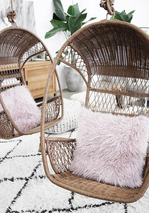 Hanging Rattan Chairs with Pink Shag Pillows