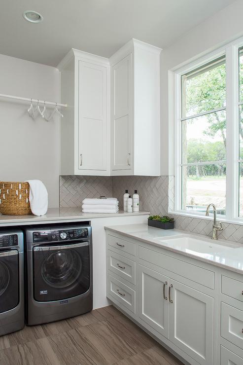 Light Gray Herringbone Tiles with White Laundry Cabinets