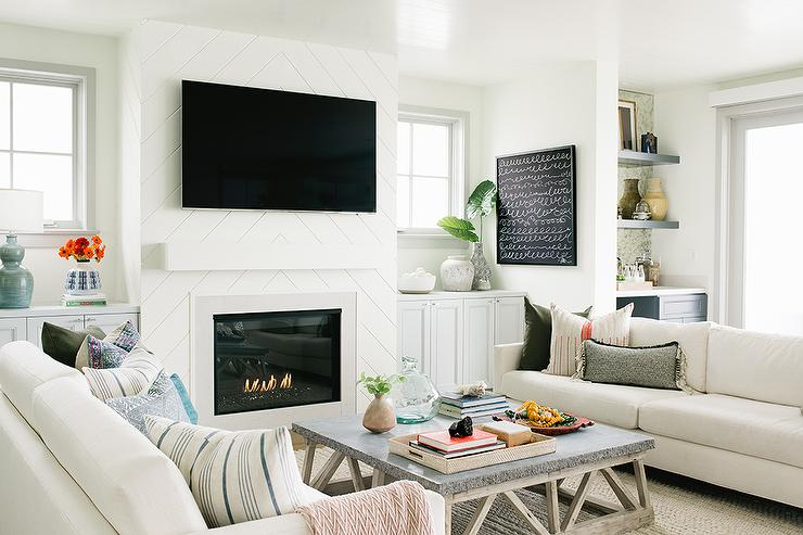 design living room with fireplace and tv wall clocks for shiplap ideas welcoming beautifully styled features a flat panel television mounted to chevron above white chunky mantel