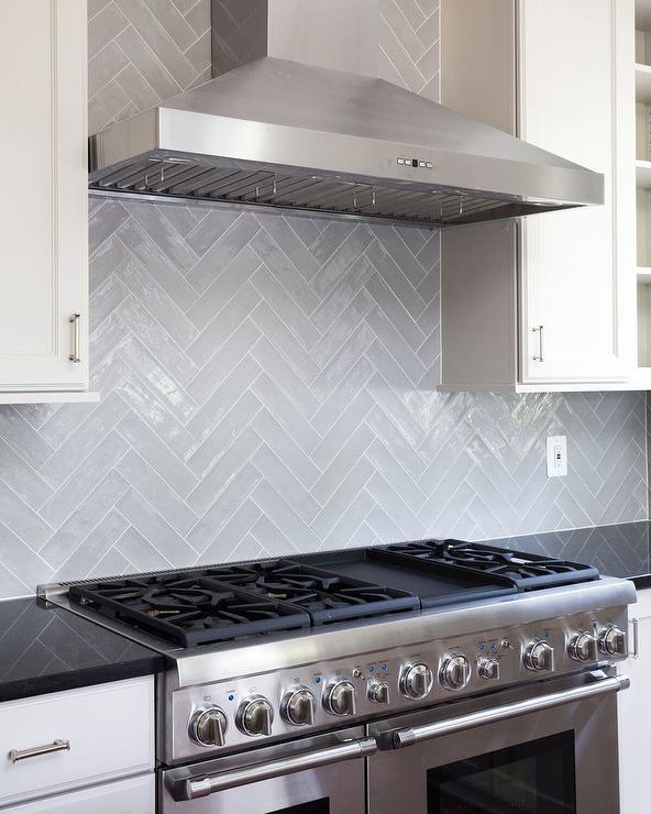 gray glazed herringbone tile backsplash