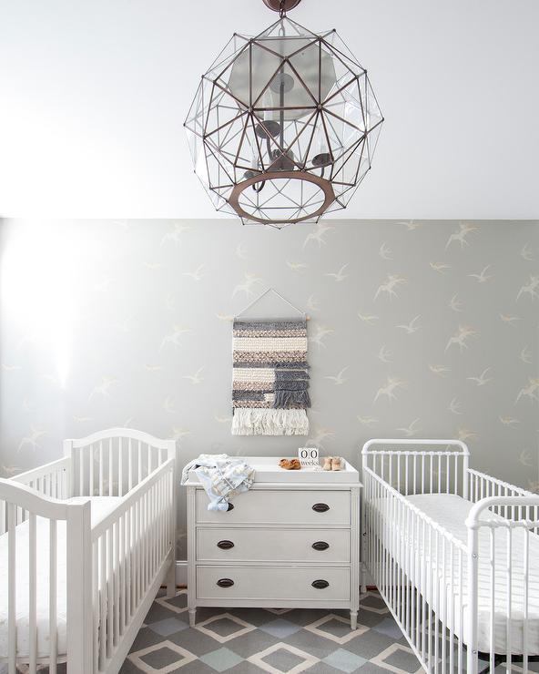 two white nursery cribs