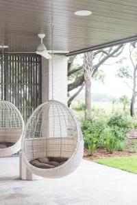 Light Gray Wicker Hanging Pod Chairs in Covered Patio