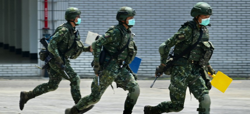 Soldiers wearing face masks amid the COVID-19 coronavirus pandemic take part in a drill during Taiwan President Tsai Ing-wen's visit to a military base in Tainan, southern Taiwan, on April 9, 2020.