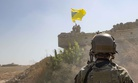 """A U.S. soldier oversees members of the Syrian Democratic Forces, or SDF, demolishing a Kurdish fighters' fortification and raising a Tal Abyad Military Council flag as part of the """"safe zone"""" near the Turkish border, Sept. 21, 2019."""