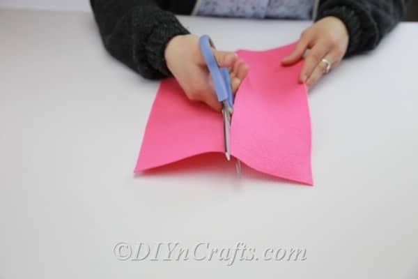 Cutting fabric in half to make DIY flowers