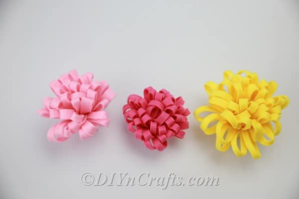 Finished DIY fabric flowers in red, yellow, and pink
