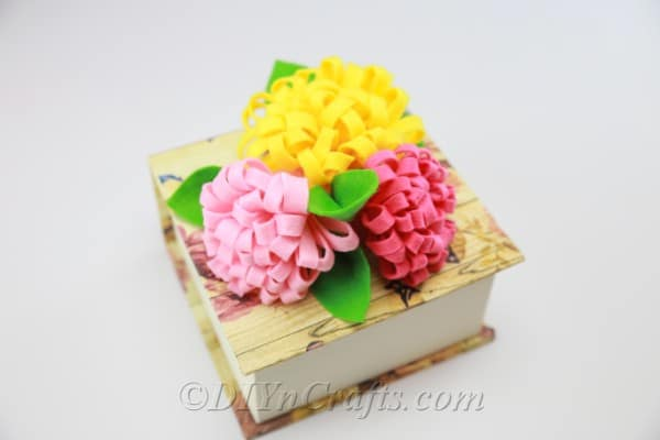 DIY fabric flowers in red, yellow, and pink with added leaves.