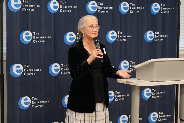 In this photo, Deb Socia, the President & CEO of The Enterprise Center, speaks to a group in front of a backdrop with The Enterprise Center's logo.